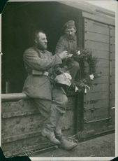 Soldier handing over a mistletoe to a fellow soldier in Germany. 1914