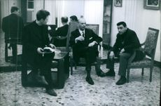 Gaston Naessens sitting and having a conversation with two other men, 1964.