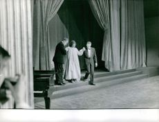Janine Charrat asisted by men as she walk stage, 1962.