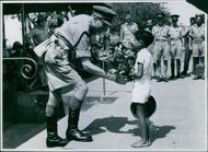 The Occupation of Madagascar A British Brigadier accepting a bouquet of tropical flowers from a French school boy. 1942