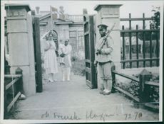 Man and woman coming out from the building, with the guard guarding outside.  1920