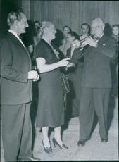 Einar Beyron and Brita Hertzberg listening to a man's trumpet during a party.