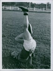 A footballer exercising in the ground, upside down.