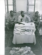 A man sitting on a couch talking with soldiers both on his side, a riffle and a lot money on the table. November 20, 1962