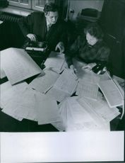 Man and woman siting and reading all the documents. 1946