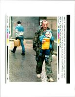 Bosnian soldier carries his son.