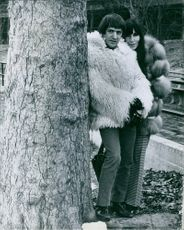 Sonny and Cher standing beside a tree wearing fur jackets.