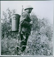 A photo of a soldier carrying a tin can in his back loaded with food during the World war I.