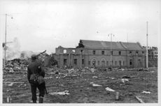 A soldier looking at a destroyed building in Finland.