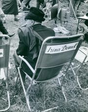 Darryl F. Zanuck is sitting on a chair what is labeled as Irina Demick.