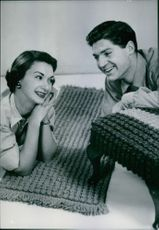 A man and a woman on the floor strike a pose and smiling.
