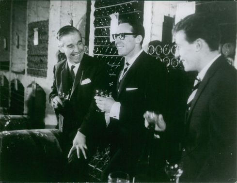 Three men having a laugh and enjoying themselves with some wine tasting.