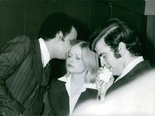 Ibrahim Houssa whispering in Ewa Aulin's ear while Nick Vernicos is talking on the phone with someone.