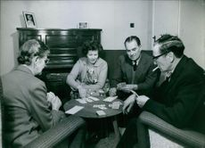 Group of four people playing cards. 1962