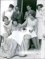 Woman sitting, holding her new born baby in her arms, other people gathered around looking at them and smiling.