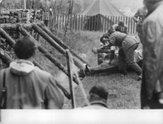 Military people treating horse.