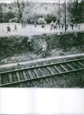 Soldiers crossover a wire fenced beside a railway during the war, France, 1963.