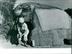 Princess Maria Gabriella coming out of a hut.