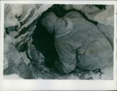 The Raid on Soroy The Norwegian policeman, being forced to dig out his papers which he had hidden in a cave. He was later taken to prison.
