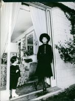 Ð?ng Tuy?t Mai standing by the door with her child.