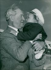 Maurice Chevalier pampering a child.