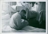 Man sitting on his bed and writing something on the paper.