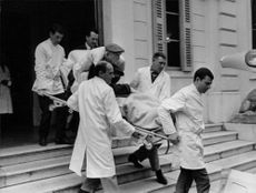 Vincent Jules Auriol being carried out on a stretcher by a team of medical assistance.