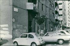 Vehicles are parked on the side street. 1972