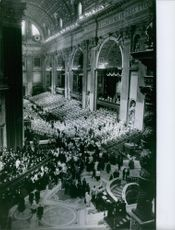 Aerial view of a huge hall, people gathered in during an event.