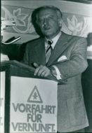 A prominent person delivering a speech in the school of Munich , 1972.