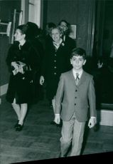 A childhood image of Crown Prince of Iran Reza Pahlavi while he in a formal dress and looking at something, some people be seen behind of him
