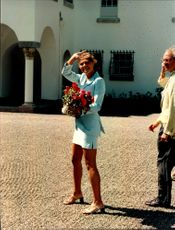 Crown Princess Victoria waves smoothly to the camera with a large bouquet of flowers in his hand during the 21st anniversary of Solliden.