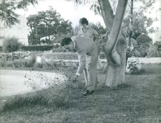 Princess Muna al-Hussein with her husband Hussein bin Talal looking at the flowers. 1961.