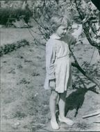 Girl standing and holding branch.