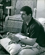 El Sayed Mustafa Ben Amer sitting on the floor with a pillow and a book.