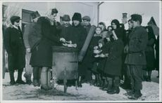 1947 Woman distributing meal, while people lining up and holding utensils.