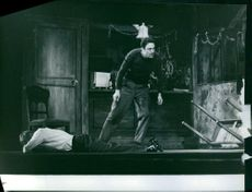 A scene of Raf Vallone and a man lying on the floor.