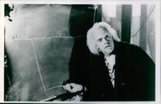 Christopher Lloyd explaining something on black board and looking in anger at someone during a scene in film Back to the Future.