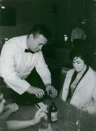 Laurent Dauthuille serving drinks to a lady as a waiter.