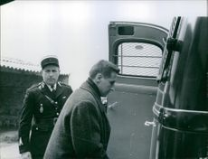 A man boarding on police van and a policeman standing behind him. 1960