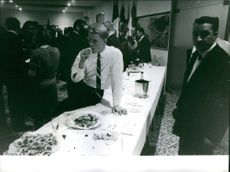Donald Arthur Schollander sitting on the table and eating in a party. December 1964