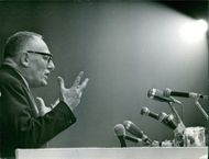 Maurice Schumann giving speech in front of many microphones.