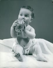 A baby putting the toy into her mouth.