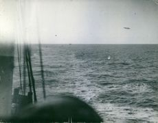 Vintage photo of a marine vessel and one of the German aircraft fleet attacked at close range. Photo take in January 1940.