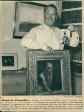Maurice Auguste Chevalier standing with a picture in his hand.