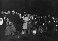 People standing in a queue with candles.