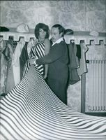 Man assisting Sherry Young to wearing a dress. Photo taken on February 9, 1961.