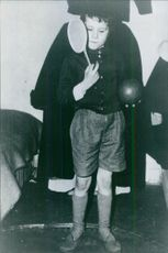 A child standing and holding ball.