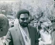 Ivan Dixon in street and communicating with other people. 1968