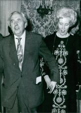 1977  A photo of a British Labour Party politician Sir Harold Wilson and his personal and political secretary Lady Falkender, holding hands for a spirited rendering of Auld Lang Syne at the former Prime Minister's farewell party in Number Ten, Downing Str